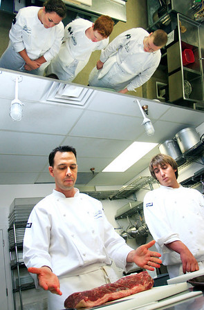 Chef Chad Armstrong (left) demonstrates how to cut and portion bison meat during the farm to table cooking class at the Culinary School of the Rockies in Boulder on Thursday, July 15.<br /> Greg Lindstrom / The Camera