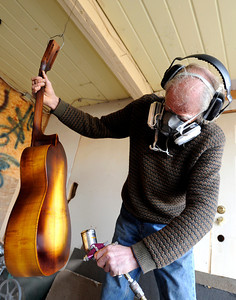 Jonas Ceelen, of Boulder, sprays a mixture of stain and polyurethane onto a custom acoustic guitar on Friday, Jan. 26, at the Jonas Guitar shop on Arapahoe Avenue in Boulder. For a video interview about the custom guitar building go to www.dailycamera.com  Jeremy Papasso/ Camera