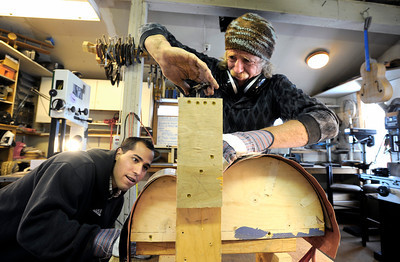 Stuart Brooks, 23, of Boulder, left, watches as Jonas Ceelen works to bend a piece of wood while building a custom guitar on Tuesday, Jan. 24, at Jonas Guitar shop at 7648 Arapahoe Rd. in Boulder. For a video of the guitar building process go to www.dailycamera.com  Jeremy Papasso/ Camera
