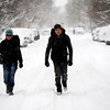 Megan Heller and Jon Mischke walk down a snowy Boulder street on their way to catch a bus to the airport. December 22, 2011<br /> Photo by Paul Aiken
