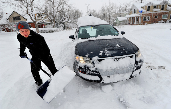 Phillip Snodgrass tries to dig out his car which was stuck on a snowy Boulder Colo. street Thursday morning. He was on his was to a job shoveling snow.  December 22, 2011<br /> Photo by Paul Aiken