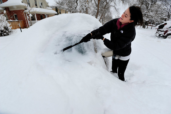 Melissa Hofstetter digs out her buried car on University HIll. December 22, 2011<br /> Photo by Paul Aiken