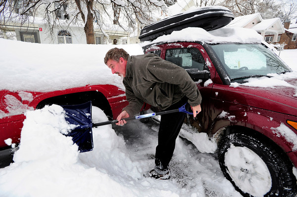 Gerry Cotton digs out his car which sits very close to another parked car on University HIll. Cotton extracted his vehicle from the situation with no damage to either car. December 22, 2011<br /> Photo by Paul Aiken