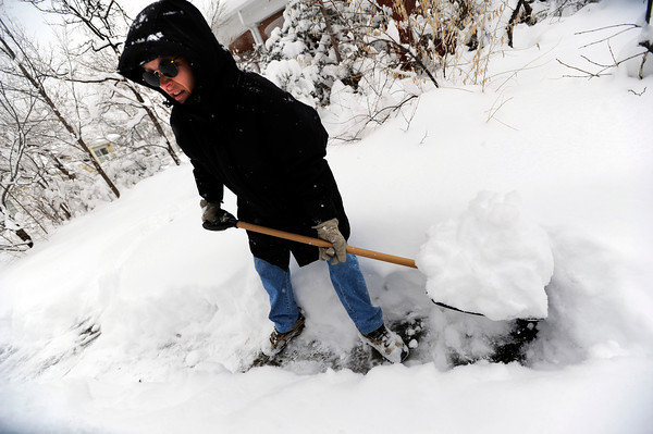 A woman who asked that her name not be used shovels snow from her Boulder sidewalk. December 22, 2011<br /> Photo by Paul Aiken