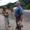 DAYTHREE<br /> Mike Duncan, a trooper with the Colorado State Patrol, accepts donations of juices from a local resident while manning the road closure at Fourmile Canyon on Wednesday. <br /> Photo by Marty Caivano/Camera/Sept. 8, 2010