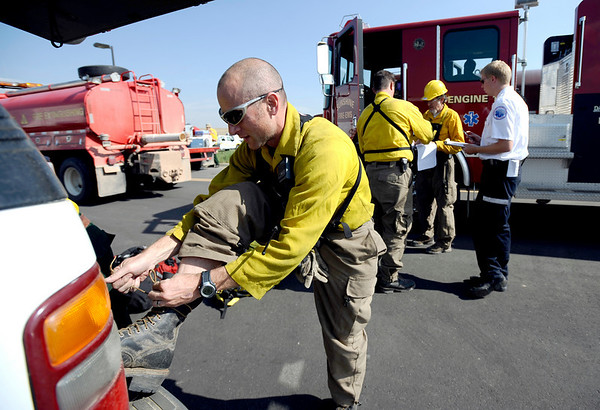 Michael Samliner, with Sunshine Fire Protection District, laces up his boots while his fire engine is being inspected at the staging area near Boulder reservoir prior to going to the Fourmile Canyon fire in Boulder, Colorado September 8, 2010.  CAMERA/Mark Leffingwell