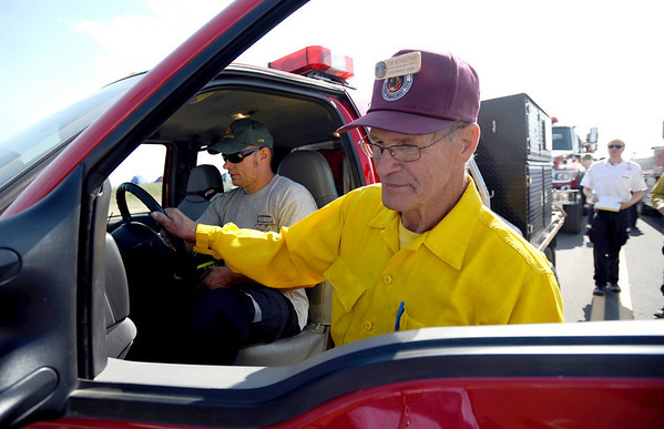 Tom Ruthleutner (right), Rocky Mountain Team A, inspects the South Metro brush fire truck whil Craig Spader (left), South Metro Fire, turns on all the lights at the staging area near Boulder reservoir prior to going to the Fourmile Canyon fire in Boulder, Colorado September 8, 2010.  CAMERA/Mark Leffingwell