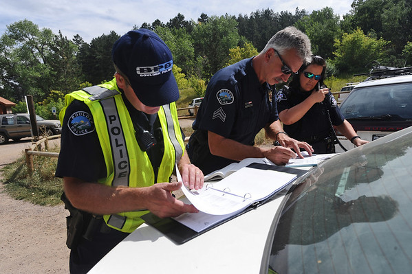 DAYTHREE<br /> Boulder Police officers including Dave Seeper, center, write a ticket for a motorist who tried to blow past the road closure on Sunshine Canyon on Wednesday. <br /> Photo by Marty Caivano/Camera/Sept. 8, 2010