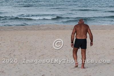 An elderly man in a bathing suit walks towards the water on a sandy beach.