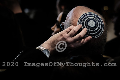 A Jewish man holds his hand to his head bearing a traditional Jewish head cover