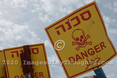 A multilingual, Hebrew, English, Arabic sign warns of danger.
