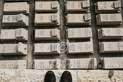 Photographer's feet stand on a ledge overlooking a section of Jewish graves and marble tombstones.