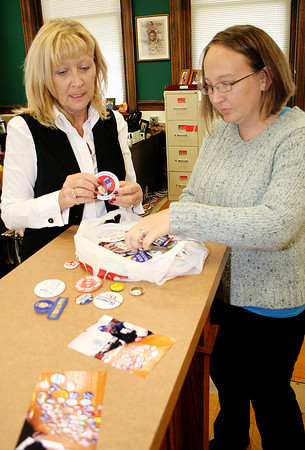 Reporter photo by Rod Rose<br /> Boone County Clerk Penny Bogan (left) and deputy clerk Jessica Fouts sift through political buttons contributed to the clerk's office by John Kelly, former history teacher at Western Boone Jr.-Sr. High School. Kelly is shown in the photo on the countertop on the day he brought the collection to the clerk's office.