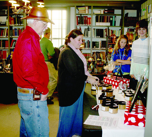 Jim Dupler, of Indianapolis, and Bryna O'Neill, of Whitestown, shop at the B. Happy Peanut Butter booth during the fourth annual Artisans' Fare Saturday, Nov. 23, at the SullivanMunce Cultural Center. Julia and Jackson Weed, at right, were helping their dad, Jon, with sales. Dupler and O'Neill were also vendors at the event: Dupler, Custom & Artistic Woodturning, makes various wood items, and O'Neill has Sage's Simple Syrups.