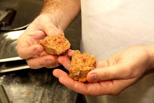 FAMILY RECIPE: Empire Pizzeria owner Alex McClelland splits a meatball in half.
