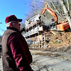 KRISTOPHER RADDER - BRATTLEBORO REFORMER<br /> Roger Hodgkins watches from a far while Brad Benjamin operates the excavator during the demolition of 42 Hyde Street in Bellows Falls on Monday, March 26, 2018.
