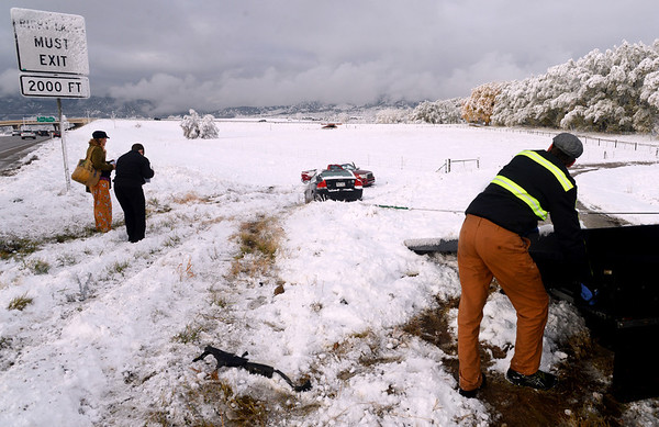 "Drivers of the cars involved in the diagonal accident  fill out accident reports while a driver from Marv's Towing pulls up one of the cars.<br /> Icy roads caused a 5-car accident on the diagonal north of Boulder and south of Jay Road Thursday morning. There were no injuries reported.<br /> For a video and more photos, go to  <a href=""http://www.dailycamera.com"">http://www.dailycamera.com</a>.<br /> Cliff Grassmick  / October 25, 2012"