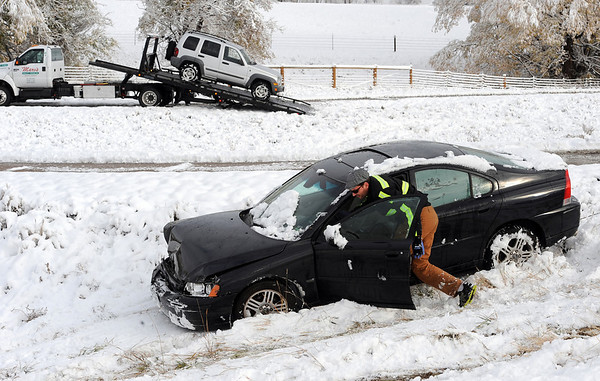 "A driver from Marv's Towing prepares a car for towing after the diagonal accident. Another car is removed in the background.<br /> Icy roads caused a 5-car accident on the diagonal north of Boulder and south of Jay Road Thursday morning. There were no injuries reported.<br /> For a video and more photos, go to  <a href=""http://www.dailycamera.com"">http://www.dailycamera.com</a>.<br /> Cliff Grassmick  / October 25, 2012"
