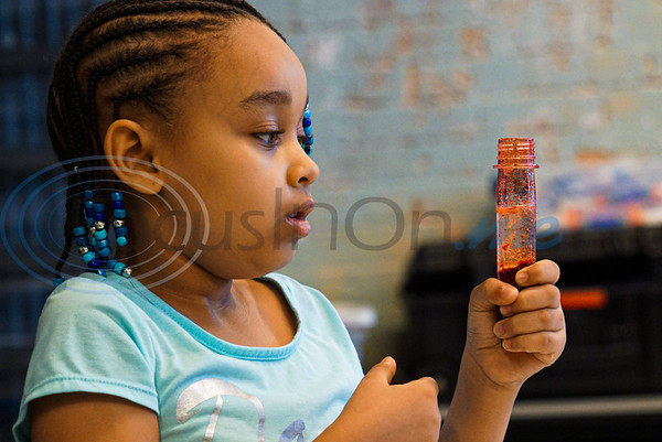 Andrea Johnson, 8, watches in amazement as her lava lamp bubbles at Discovery Science Place's Chemical Engineering camp.