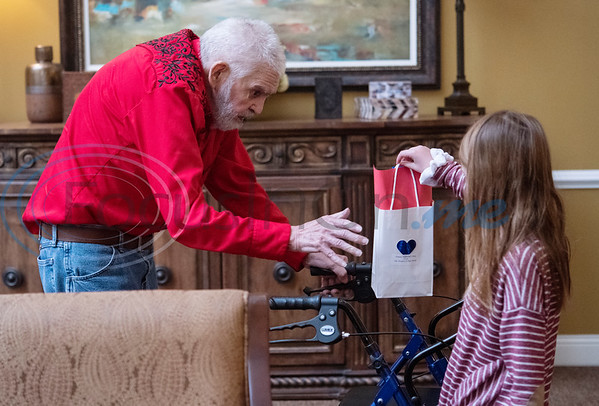 "Leighton Johnson, 7, of Troup, hands out a Valentine's Day bag with a card from Dixie Elementary students to Air Force veteran Kenneth ""Ralph"" Kinney at Park Place Nursing and Rehabilitation Center in Tyler on Monday, Feb. 10, 2020. Johnson's mother is Suzanne Johnson of Hospice of East Texas which partnered with Dixie Elementary School to make Valentine's Day cards for local veterans.   (Sarah A. Miller/Tyler Morning Telegraph)"