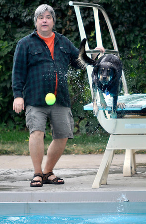 Ken Strassberg throws the ball as Sadie Sue jumps off the diving board during the annual Dog Dayz at Scott Carpenter Pool in Boulder, Colorado Monday September 17, 2012. Every year the pool is opened to dogs after the regular season is over and closed to humans. DAILY CAMERA/ JESSICA CUNEO