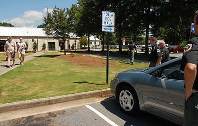 "08-10-11  --dogs locked in 05--  After numerous pages in the Cobb County Animal Control building and having an Animal Control Officer go through the building to find the owners, Dominick Lovin of Marietta and his wife walk back to their car at 12:30 p.m. as Animal Control Officers wait for them. The couple claimed to have ""only been inside for five minutes."" The sign in sheet inside the building stated they arrived at 12:00 and I arrived at 12:16. STAFF/LAURA MOON."