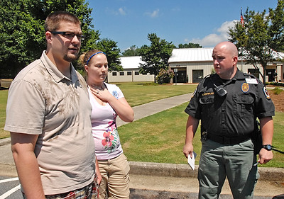 08-10-11  --dogs locked in 06--  Cobb County Animal Control officers question the Marietta couple as to why they left the dogs in the car and stress the dangers of leaving them in the heat. STAFF/LAURA MOON.