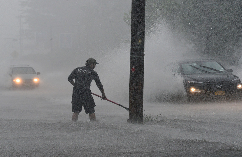 KRISTOPHER RADDER — BRATTLEBORO REFORMER<br /> Owen Toleno, an employee at Top of the Hill Grill, uses a rake to remove debris from the drain as the water backs up onto Putney Road during a rainstorm that passed through the area on Wednesday, Aug. 7, 2019.
