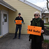 Dracut Housing Authority executive director Mary Karabatsos of Newburyport, and maintenance tech Jim Murphy of Dracut, with signs that residents have been given to put in their doors to show if they're okay or in need of help. (SUN/Julia Malakie)