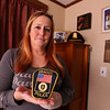 Gail Paquin of Dracut, whose late father, Robert W. Paquin, a Dracut Police captain who spent time as acting chief, with the patch he designed, and which is still in use but soon to be replaced. At rear is memorabilia of her father. (SUN/Julia Malakie)