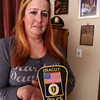 Gail Paquin of Dracut, whose late father, Robert W. Paquin, a Dracut Police captain who spent time as acting chief, with the patch he designed, and which is still in use but soon to be replaced. (SUN/Julia Malakie)