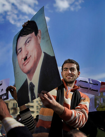 An anti-government protester being carried on the shoulders of another holds up a portrait of Egyptian President Hosni Mubarak on which he had drawn a moustache and hair in black to represent Adolf Hitler, to loud cheers from the crowd, at the continuing demonstration in Tahrir square in downtown Cairo, Egypt, Monday, Jan. 31, 2011. A coalition of opposition groups called for a million people to take to Cairo's streets Tuesday to demand the removal of President Hosni Mubarak. (AP Photo/Ben Curtis)