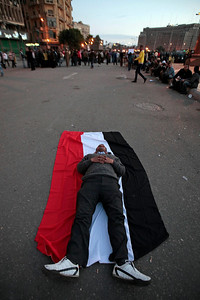 A man rests on an Egyptian flag in Cairo, during a demonstration by anti-government protesters, in Cairo's Tahrir Square, Egypt, Monday, Jan. 31, 2011. A coalition of opposition groups called for a million people to take to Cairo's streets Tuesday to demand the removal of President Hosni Mubarak. (AP Photo/Lefteris Pitarakis)