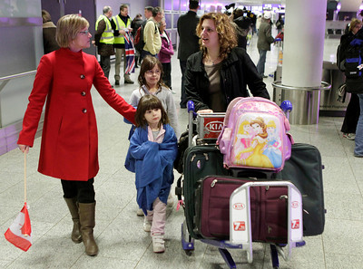 A Canadian mother and her two children are welcomed by an employee of the Canadian Embassy at the airport of Frankfurt, central Germany, early Tuesday, Feb. 1, 2011,  after they were flown out of Cairo by Air Canada. (AP Photo/Michael Probst)