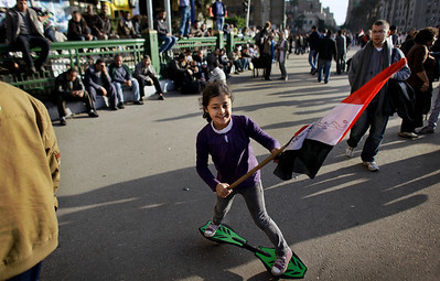 A young Egyptian anti-government protester holding an Egyptian flag skateboards amongst the crowd at the continuing demonstration in Tahrir square in downtown Cairo, Egypt, Monday, Jan. 31, 2011. A coalition of opposition groups called for a million people to take to Cairo's streets Tuesday to demand the removal of President Hosni Mubarak. (AP Photo/Ben Curtis)