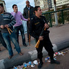 An Egyptian police officer stands guard next to one of the many neighborhood watch groups of men armed with metal bars and sticks at a checkpoint leading  to a bridge in Cairo, Egypt, Monday, Jan. 31, 2011. A coalition of opposition groups called for a million people to take to Cairo's streets Tuesday to demand the removal of President Hosni Mubarak. (AP Photo/Emilio Morenatti)