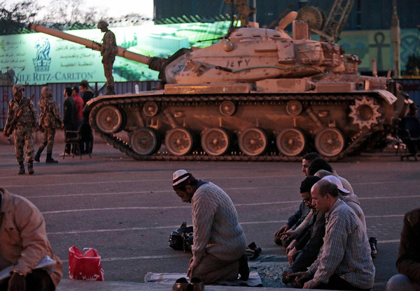 Anti-government protesters offer their evening prayers, in front of an Egyptian army tank securing the area, during a protest in Cairo's Tahrir Square, Egypt, Monday, Jan. 31, 2011. A coalition of opposition groups called for a million people to take to Cairo's streets Tuesday to demand the removal of Egyptian President Hosni Mubarak. (AP Photo/Lefteris Pitarakis)