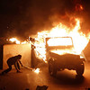 In this photo released by China's Xinhua News Agency, a police vehicle is set on fire by anti-government demonstrators in Cairo, capital of Egypt, on Friday, Jan. 28, 2011. Protesters have seized the streets of Cairo, battling police with stones and firebombs, burning down the ruling party headquarters, and defying a night curfew enforced by a military deployment. (AP Photo/Xinhua, Cai Yang) NO SALES