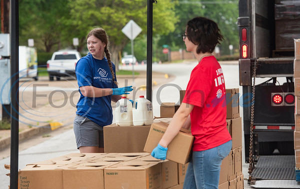 Volunteers Hannah Lehman and Bailey Johnson work at the ETFB drive-thru emergency food box distribution in response to COVID-19 in Tyler, Texas on Friday, April 3, 2020. According to officials from the East Texas Food Bank, 840 households were served in the drive-thru with 1680 gallons of milk and 13,440 meals.