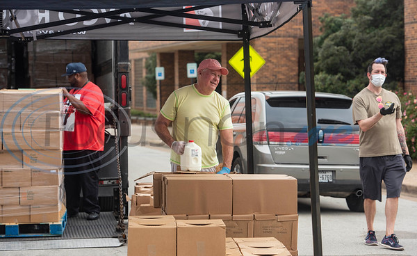 East Texas Food Bank warehouse staff member Quinlyn Roberts unloads boxes of food from a truck while volunteer Mike Means unpacks gallons of milk and volunteer Coby Archa signals for cars to move up in line at a drive-thru emergency food box distribution in response to COVID-19 in Tyler, Texas on Friday, April 3, 2020. According to officials from the East Texas Food Bank, 840 households were served in the drive-thru with 1680 gallons of milk and 13,440 meals.