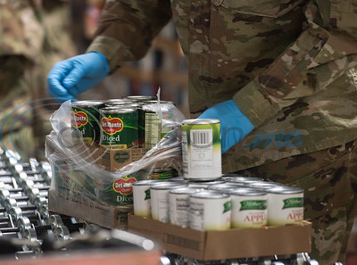 Members Texas Army National Guard unpack canned goods to sort into family boxes at the East Texas Food Bank in Tyler, Texas on Wednesday, April 15, 2020.  In response to COVID-19, 34 Texas Army National Guardsmen have been deployed to the East Texas Food Bank to ensure that the agency can continue to safely meet the need for food assistance in its 26-county coverage area. The deployment comes after the Smith County Emergency Operations Center submitted a STAR request for the guardsmen to support ETFB with its production, distribution and transportation tasks through May.