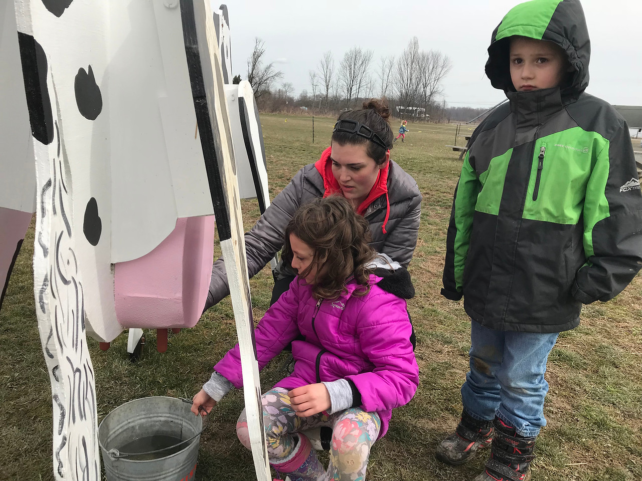 NATHAN HAVENNER / GAZETTE  Madelyn Aliff, 8, Eli Sawyer, 6, and Ashley Blagg of North Ridgeville check out a wooden cow that teaches kids how cows are milked during the Easter Egg Hunt and Farm Fun event at Beriswill Farms, 2200 Station Road, Liverpool Township.