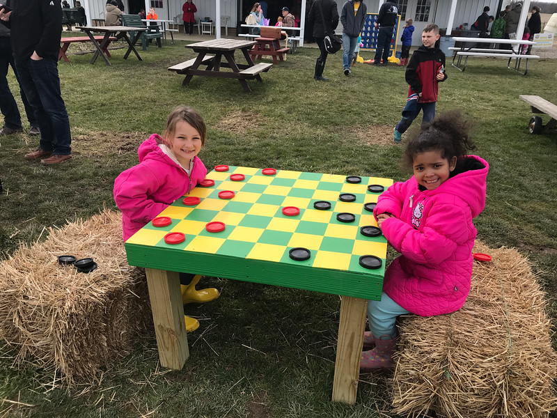 NATHAN HAVENNER / GAZETTE  Taylor, 8, left, and London Popil, 5, of Medina, play a game of giant checkers at Beriswill Farms, 2200 Station Road, Liverpool Township, on Saturday during the Easter Egg Hunt and Farm Fun event.