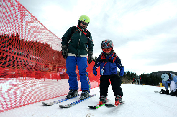 """Carl Swanson and his 4-year-old son Tobin, of Longmont, work their way towards the chairlift on opening day on Friday, Nov. 16, at Eldora Mountain Resort. For more photos and video of opening day go to  <a href=""""http://www.dailycamera.com"""">http://www.dailycamera.com</a><br /> Jeremy Papasso/ Camera"""