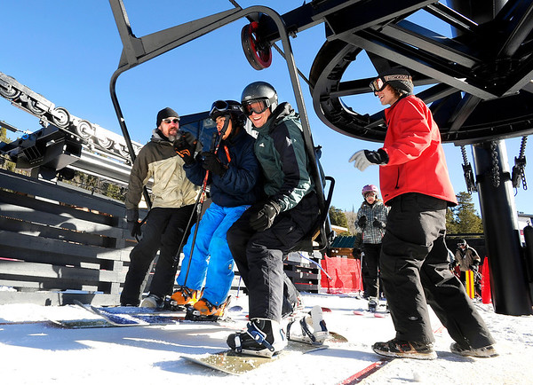 """Eldora lift operator Ben Davis, right, watches as Glenn Miller, of Longmont, left, Eliot Lee, of Blackhawk, center, and Keith Speckman, of Boulder, ride the first chair on opening day at Eldora Mountain Resort on Friday, Nov. 18. For more photos and video of opening day go to  <a href=""""http://www.dailycamera.com"""">http://www.dailycamera.com</a><br /> Jeremy Papasso/ Camera"""