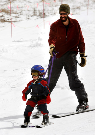 "Micah Lafaiver, 3, left, and his father Steven Lafaiver, right, ski down the bunny slope at Eldora Mountain Resort on the last day of the seasion season at on Sunday, April, 15, 2012, Boulder. This was Micah's first time skiing. <br /> Photo by Derek Broussard<br /> For more photos and video visit  <a href=""http://www.dailycamera.com"">http://www.dailycamera.com</a>"