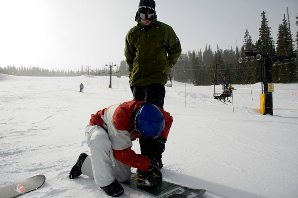 CU freshman Bree Karnes buckles the boots of first time snowboarder and freshman Ethan Nyeste at Eldora Ski Resort near Nederland, Thursday, Dec. 17, 2009. Eldora is seeing better and more snow than usual, and is working on opening up terrain parks and back bowls early this season. <br />  <br /> KASIA BROUSSALIAN