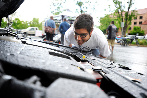 "Danny Caballero, of Boulder, looks at the engine of an electric car on Thursday, May 17, during the electric vehicle expo outside of the Wolf Law building on the University of Colorado campus in Boulder. For more photos and video of the event go to  <a href=""http://www.dailycamera.com"">http://www.dailycamera.com</a><br /> Jeremy Papasso/ Boulder Daily Camera"