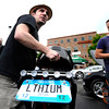 "University of Colorado research associate Noah Podolefsky, left, removes the seat from his custom built electric motorcycle to show Dan Perata, of Boulder, right, the electrical components on Thursday, May 17, during the electric vehicle expo outside of the Wolf Law building on the University of Colorado campus in Boulder. For more photos and video of the event go to  <a href=""http://www.dailycamera.com"">http://www.dailycamera.com</a><br /> Jeremy Papasso/ Boulder Daily Camera"
