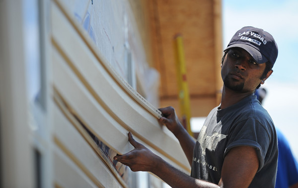 Globe/T. Rob Brown<br /> Rohan Bathula, 23, from First United Methodist Church in Elgin, Ill., adds siding to a Rebuild Joplin home for Emily Morrison, Thursday morning, June 13, 2013.